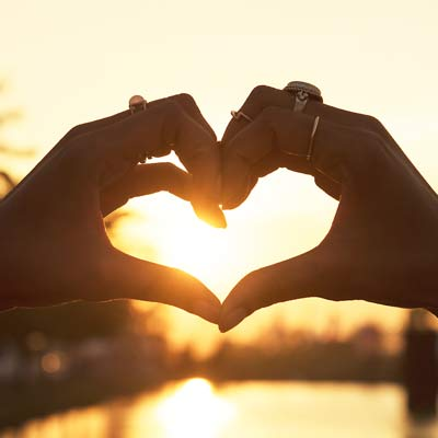 Hands in heart shape with sunlight shining through